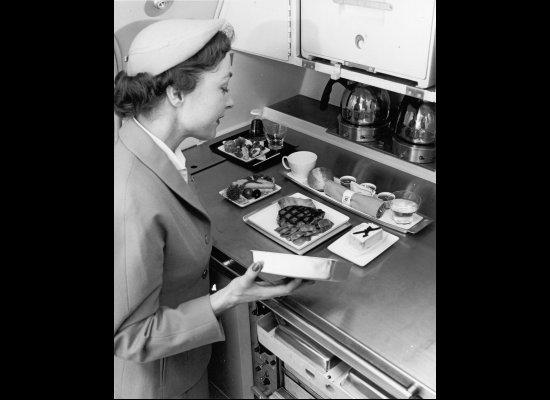 Pramugari United Airlines sedang mempersiapkan hidangan untuk penumpang di galley. Foto ini diambil sekitar tahun 1940an.